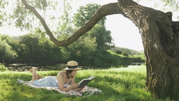 Thumbnail for Lady in straw hat and dress lying on blanket on meadow in park by the river and reading book