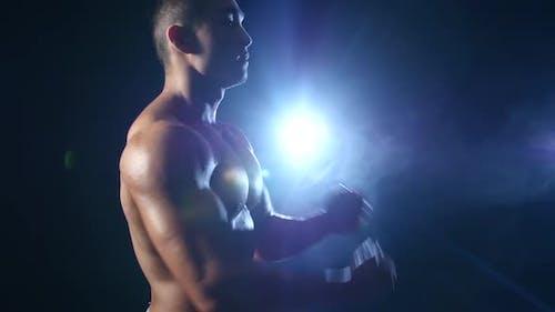 Asian Bodybuilder demonstriert seinen Körper, Kraft und Ausdauer. Black Smoke Hintergrund