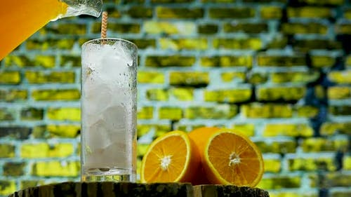 Yellow Lemonade With Ice And Orange Slices. Pour Orange Juice Into A Glass
