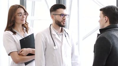 Three Medical Workers Having a Conversation at Clinic