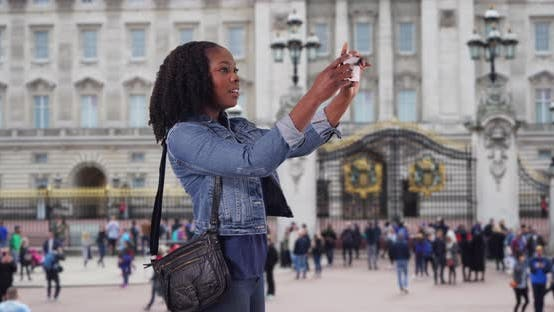Thumbnail for Cute African American female at Buckingham Palace taking picture with smartphone