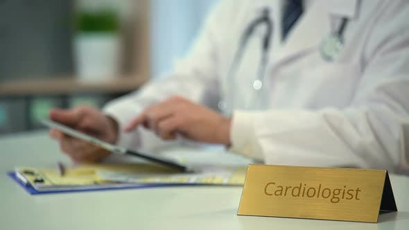 Thumbnail for Cardiologist Browsing on Tablet PC in Clinic, Consulting Patients Online
