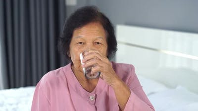 senior woman drinking water in the bedroom