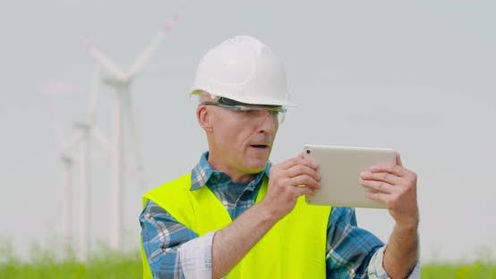 Thumbnail for Male Engineer Video Conferencing Against Windmills