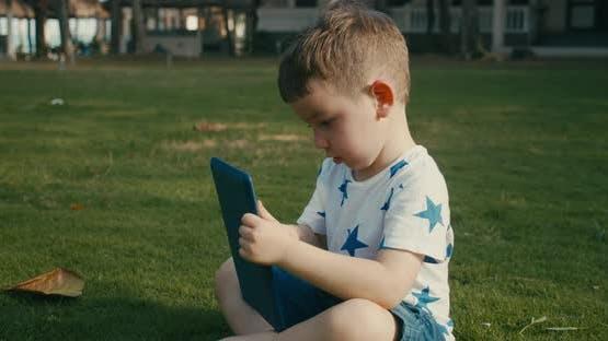 Curious Cute Baby Boy Preschool Child Using a Digital Tablet Technology Device Looks Telephone