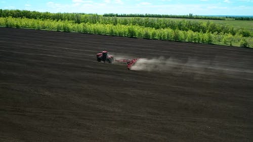 Tractor Processes the Land for Seeding, Dust Flies. Agricultural Work for Sowing Grain. Side View