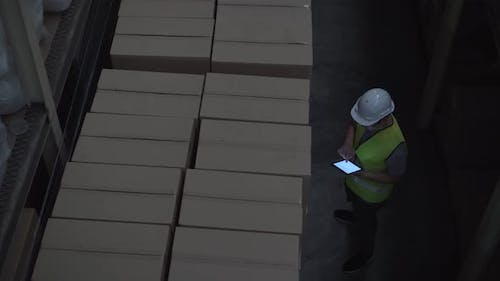 Warehouse Worker Man with Safety Hard Hat is Checking Order Details with Tablet at Inventory Room
