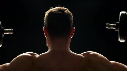 Close Up Muscular Man Lifting Dumbbells.