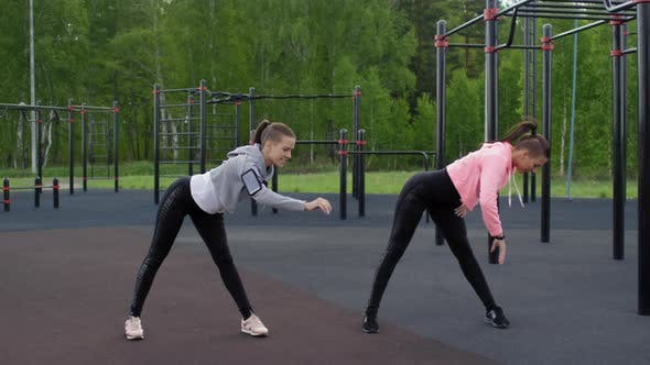 Cover Image for Caucasian Twin Sisters Warming Up at Outdoor Workout Stadium