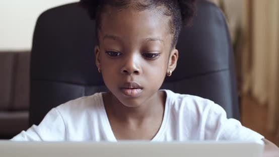 Thumbnail for Portrait of Concentrated Child Preschool Girl Pupil Looking at Laptop Screen Studying Remotely