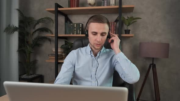 Thumbnail for Caucasian Man, Call Center Agent in Headset Consult Business Client Online Using Laptop