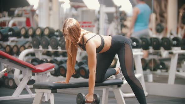 Thumbnail for An Athlete Woman with Long Hair Training in the Gym - Training Her Arms - Pulling the Dumbbell While