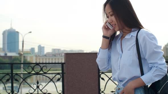 Thumbnail for Pretty Brunette Walking on Riverside and Talking on Phone