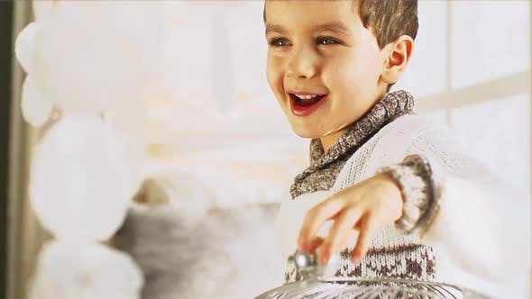 Thumbnail for Portrait Of A Cute Little Boy On A Windowsill In The Winter At Home