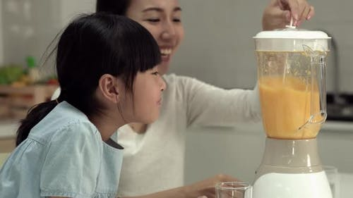 Woman and little girl with electric blender