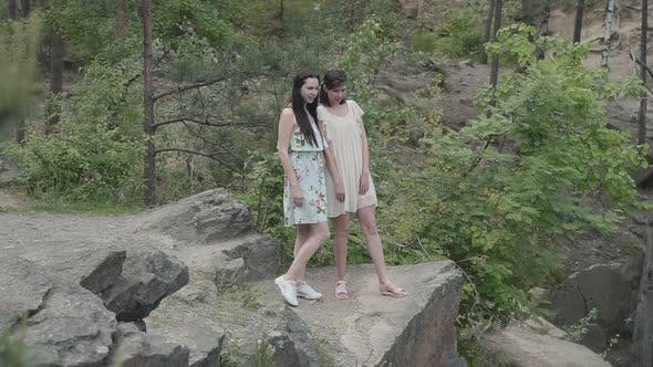 Thumbnail for Portrait Two Beautiful Women in Short Dresses Standing on Rocky Ground with Wild Flowers and Looking