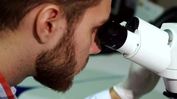 Thumbnail for Man Looks Into the Eyepieces of Microscope at the Laboratory