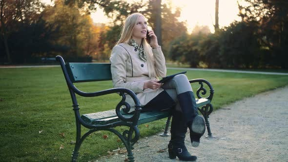 Young Blonde Girl with Tablet Computer and Cellphone Sitting on Park Bench.