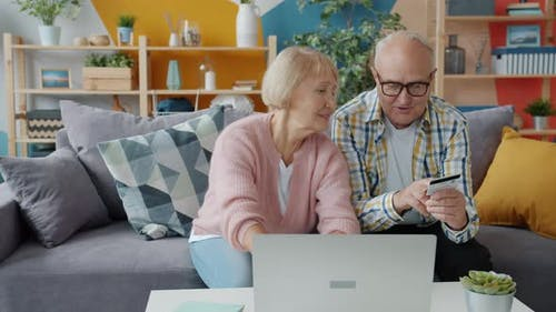 Senior Husband and Wife Making Electronic Payment with Bank Card and Laptop
