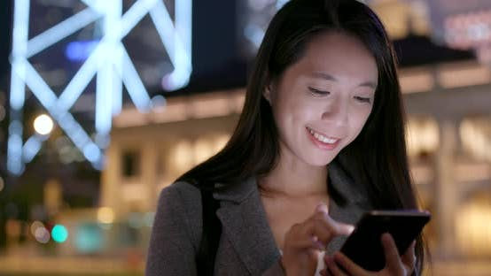 Thumbnail for Businesswoman use of smart phone in city at night