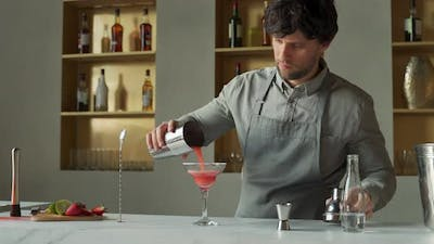 Bartender Pours a Cocktail in a Margarita Glass Decorates the Glass with Lime and Strawberries