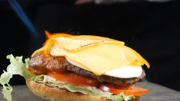 Thumbnail for Cook Using Blow Torch To Melt Cheese on Meat Cutlet of Burger. Slow Motion Food Video. Burger