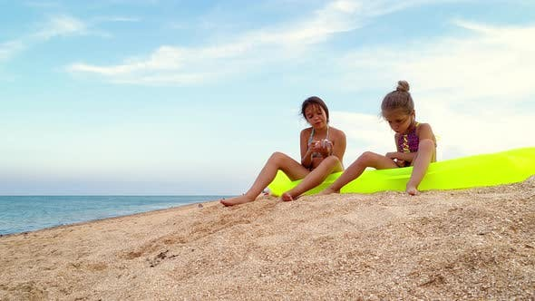 Little Girls Relaxing on an Air Mattress at the Seaside