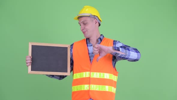 Thumbnail for Stressed Young Man Construction Worker Holding Blackboard and Giving Thumbs Down