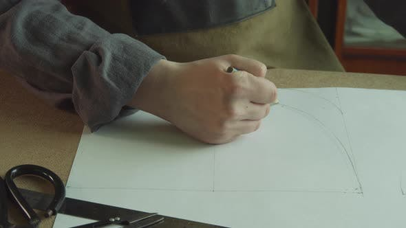 The Tailor's Hand with a Pencil Draws the Shape of the Patterns for the Author's Shoes on Paper.