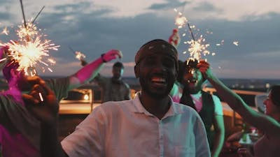 Happy African-American Man with Sparkler at Party