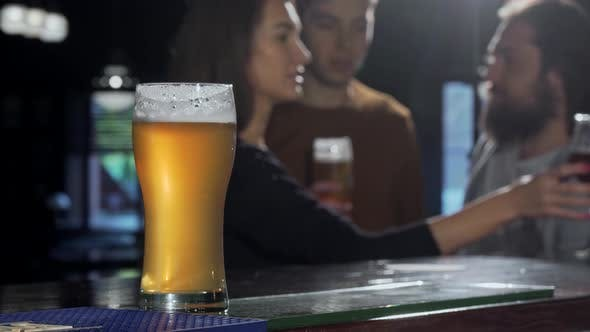 Thumbnail for Selective Focus on a Beer Glass, People Drinking at the Pub on the Background
