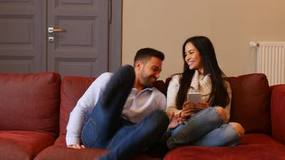 A young couple discussing content on a smartphone