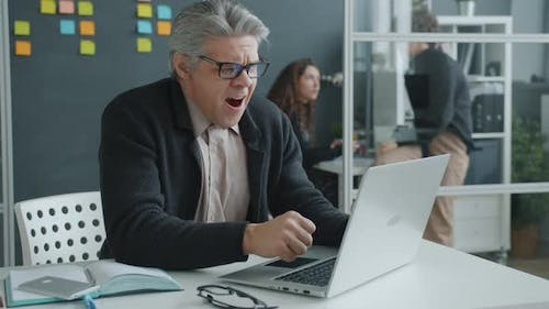 Exhausted Mature Man Working with Laptop Typing Then Yawning Feeling Sleepy in Workplace