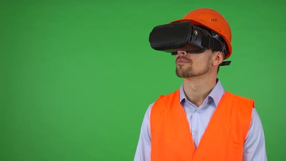 Thumbnail for A Young Construction Worker Uses VR Glasses - Green Screen Studio - He Looks Around