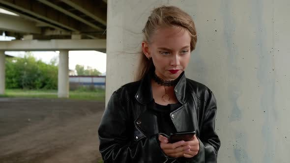 Young Girl in Black Leather Jacket Using Mobile Phone on City Street
