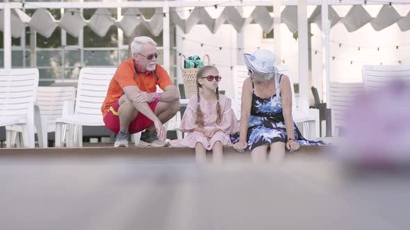 Cover Image for Happy Mature Couple with Little Granddaughter on the Edge of the Luxury Pool
