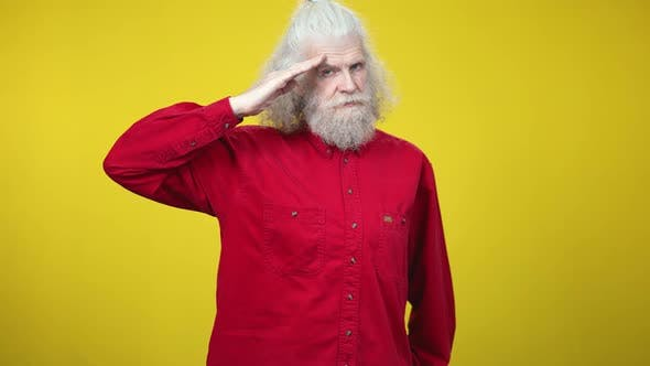 Handsome Confident Senior Man Saluting on Yellow Background Looking at Camera