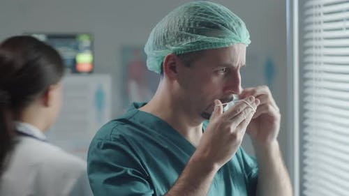 Male Healthcare Worker Putting on Face Mask in Clinic