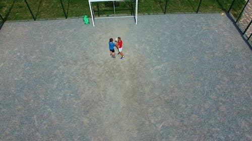 Children playing on playground. Top down aerial view of children playing on sports field