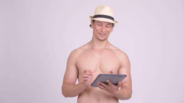 Thumbnail for Happy Muscular Tourist Man Thinking While Using Digital Tablet Shirtless