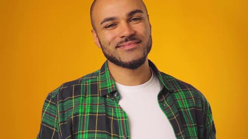 Young African American Man in Casual Shirt Smiling and Raising Eyebrows Against Yellow Background