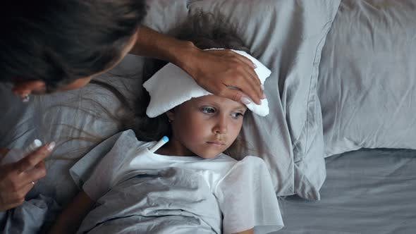 Thumbnail for Sick girl with a thermometer and compress on forehead lying in bed