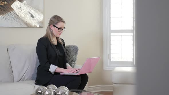 Thumbnail for Revealing A Young Female Business Entrepreneur Typing On Her Laptop Computer In A Living Room 1