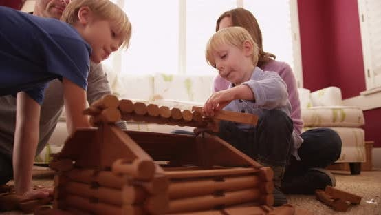 Thumbnail for Adorable young children building a wooden house with family