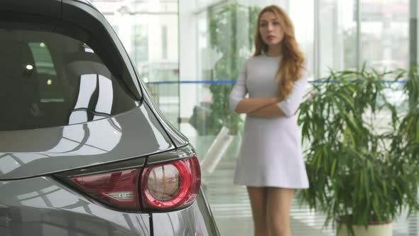 Thumbnail for Beautiful Woman Thinking While Choosing a New Car at the Dealership