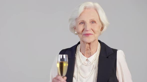Cover Image for Happy Senior Woman Raising Champagne Glass