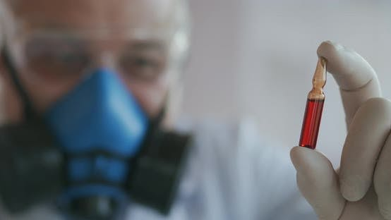 Extreme Close-up of a Scientist in a Blue Respirator and Protective Glasses, a Developer of a