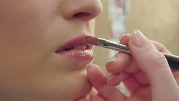 Thumbnail for Makeup Artist Uses Brush To Apply Lip Gloss To Model Lips