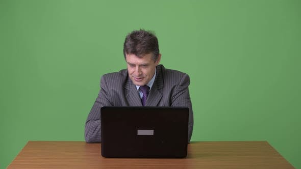 Thumbnail for Mature Handsome Businessman Against Green Background
