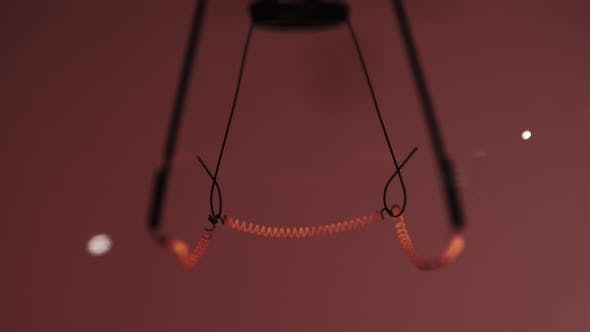 The Tungsten Filament in a Glass Lamp Closeup in Slow Motion on Red Background